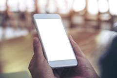 Mãos que guardam o telefone celular branco com a tela vazia do desktop com fundo do borrão Foto de Stock Royalty Free