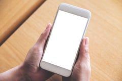 Mãos que guardam o telefone celular branco com a tela vazia do desktop na tabela de madeira no café Imagem de Stock Royalty Free