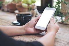 Mãos que guardam o telefone celular branco com a tela vazia do desktop com uma xícara de café na tabela de madeira no café Foto de Stock