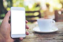 Mãos que guardam o telefone celular branco com tela vazia e o copo de café quente na tabela de madeira com fundo da natureza do v Imagens de Stock