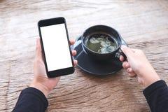 Mãos que guardam o telefone celular preto com a tela branca vazia do desktop e uma xícara de café na tabela de madeira no café Imagem de Stock Royalty Free