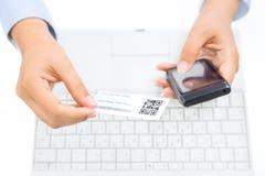 Mãos que guardam o telefone e o cartão espertos com código do qr Fotos de Stock Royalty Free