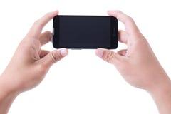 Mãos que guardam o telefone esperto móvel com a tela vazia isolada em w Imagem de Stock Royalty Free