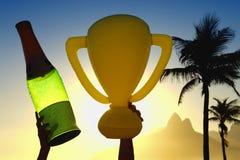 Mãos que guardam o troféu e o Champagne Bottle Rio de janeiro Skyline Imagem de Stock