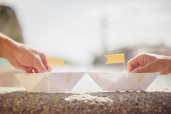 mãos que guardam os barcos de papel no verão Fotografia de Stock
