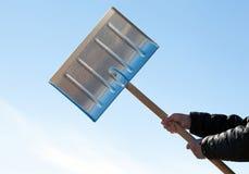 Mãos que guardam a pá para a remoção de neve fotos de stock