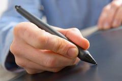 Mãos que guardam a pena da tabuleta gráfica Imagens de Stock