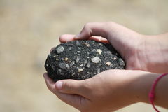 Mãos que guardam a rocha foto de stock royalty free