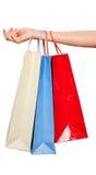 Mãos que guardam sacos de compras coloridos no fundo branco Fotografia de Stock