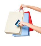 Mãos que guardam sacos de compras coloridos no fundo branco Fotos de Stock Royalty Free