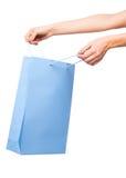 Mãos que guardam sacos de compras coloridos no fundo branco Imagens de Stock