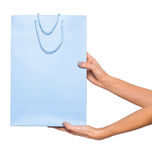 Mãos que guardam sacos de compras coloridos no fundo branco Fotografia de Stock Royalty Free