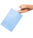 Mãos que guardam sacos de compras coloridos no fundo branco Foto de Stock