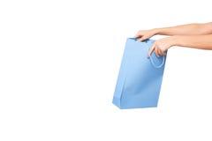 Mãos que guardam sacos de compras coloridos no fundo branco Foto de Stock Royalty Free