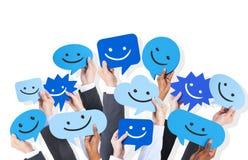 Mãos que guardam Smiley Face Icons imagens de stock royalty free