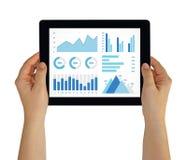 Mãos que guardam a tabuleta com elementos dos gráficos e das cartas na tela Imagens de Stock