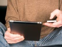 Mãos que guardam a tabuleta e o smartphone Imagens de Stock