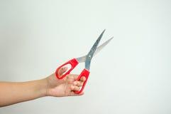 Mãos que guardam tesouras vermelhas Imagens de Stock