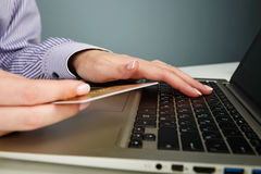 Mãos que guardam um cartão de crédito Imagens de Stock