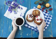 Mãos que guardam um copo azul Café da manhã com biscoitos e as bagas frescas Fotografia de Stock Royalty Free