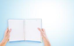 Mãos que guardam um livro vazio Fotografia de Stock Royalty Free