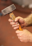 Mãos que guardam um martelo Foto de Stock