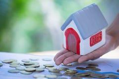Mãos que guardam um modelo da casa Plano da hipoteca da indústria de alojamento e estratégia de economia residencial do imposto,  foto de stock royalty free