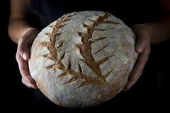 Mãos que guardam um naco de pão caseiro imagem de stock