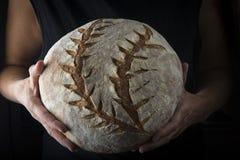 Mãos que guardam um naco de pão caseiro imagens de stock