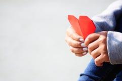Mãos que guardam um papel vermelho da forma do coração foto de stock