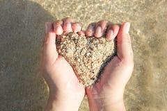 Mãos que guardam uma areia no formulário do coração fotografia de stock