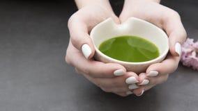 Mãos que guardam uma bacia com chá do matcha fotografia de stock royalty free