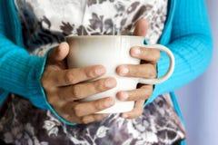 Mãos que guardam uma caneca Fotos de Stock Royalty Free