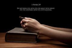 Mãos que guardam uma cruz na Bíblia Sagrada com verso imagens de stock royalty free