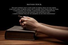 Mãos que guardam uma cruz na Bíblia Sagrada com verso imagens de stock