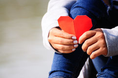Mãos que guardam uma forma vermelha do coração fotografia de stock royalty free
