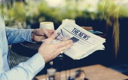Mãos que guardam uma leitura do jornal no café fotografia de stock royalty free