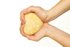 Mãos que guardam uma massa limpa terminada na forma do coração imagem de stock