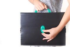 Mãos que guardam uma pasta preta técnica velha e arruinada Imagem de Stock Royalty Free