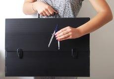 Mãos que guardam uma pasta preta técnica velha e arruinada Fotografia de Stock