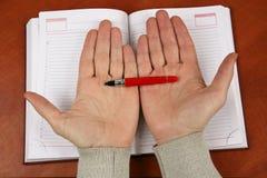 Mãos que guardam uma pena vermelha sobre um caderno aberto Imagens de Stock Royalty Free