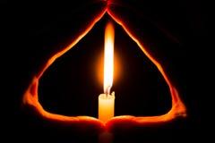 Mãos que guardam uma vela ardente na obscuridade Imagens de Stock