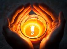 Mãos que guardam vela ardente Imagens de Stock Royalty Free