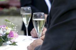 Mãos que guardam vidros do champanhe e do vinho imagem de stock