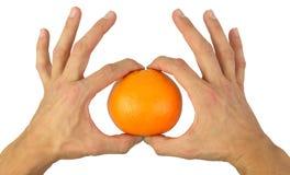 Mãos que guardaram delicadamente uma laranja Fotografia de Stock Royalty Free