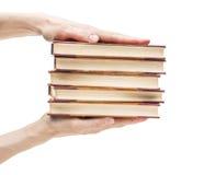 Mãos que guardaram a pilha de livros velhos Fotos de Stock Royalty Free