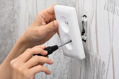 Mãos que instalam um soquete de poder da parede Fotografia de Stock