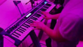 Mãos que jogam o piano Dedos no piano, luzes das cores video estoque