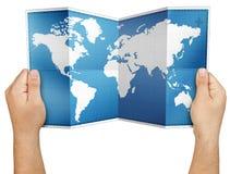Mãos que mantêm o mapa do mundo dobrado aberto isolado imagem de stock