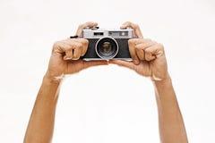 Mãos que mantêm uma câmera de Wintage isolada no branco Fotografia de Stock Royalty Free
